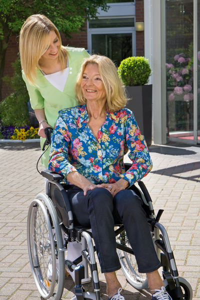 Nurse-with-Senior-Lady-in-Wheelchair-Outdoors-000068919219_Full