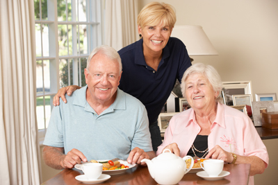 Senior-Couple-Enjoying-Meal-Together-With-Home-Help-000020442950_Full