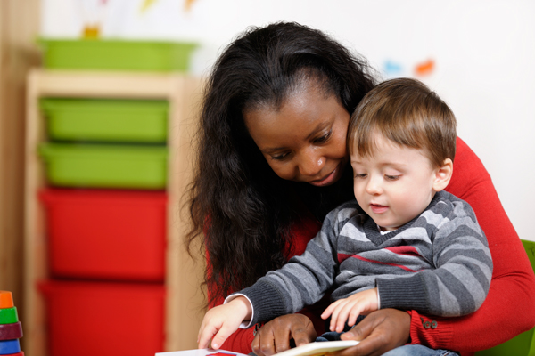 Toddler-Enjoying-Storytime-With-His-Carer-000015241731_Full