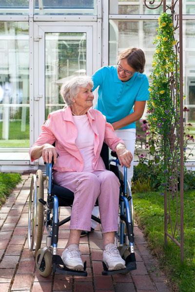 Elderly-lady-in-a-wheelchair-with-her-carer-000048917298_Full